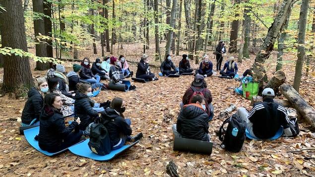 Des étudiants assis en rond sur des tapis dans une forêt.