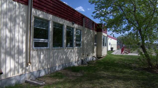 Façade extérieur de classes portatives avec un arbre et un parc pour enfants à l'arrière.