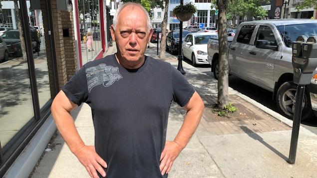 Un homme pose les mains sur les hanches, sérieux, au centre-ville de Rouyn-Noranda.