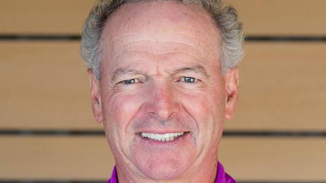 Un homme portant un polo de golf sourit à la caméra.