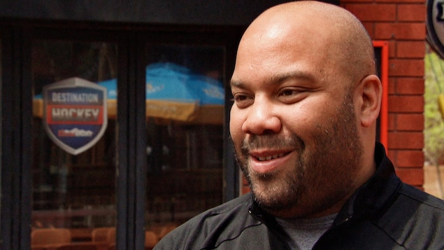 Un homme en entrevue devant un restaurant.