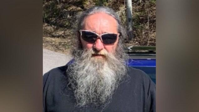 Photo de Claude Godin : Homme de 57 ans, avec une barbe et cheveux longs de couleur grise. Sur la photo, il porte des lunettes fumées.