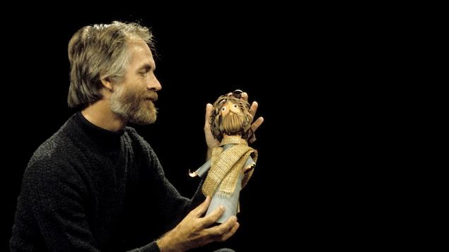 Dans un studio de télévision, Claude Lafortune avec un personnage en papier dans ses mains.