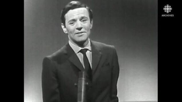 Plan buste de Claude Léveillée qui chante au micro.