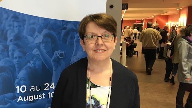 Claudette Thériault devant une affiche du Congrès mondial acadien 2019.
