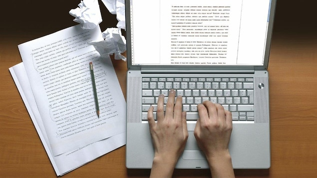 Une personne rédigeant un texte à l'ordinateur