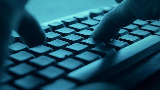 Un homme tape sur un clavier dans le noir.