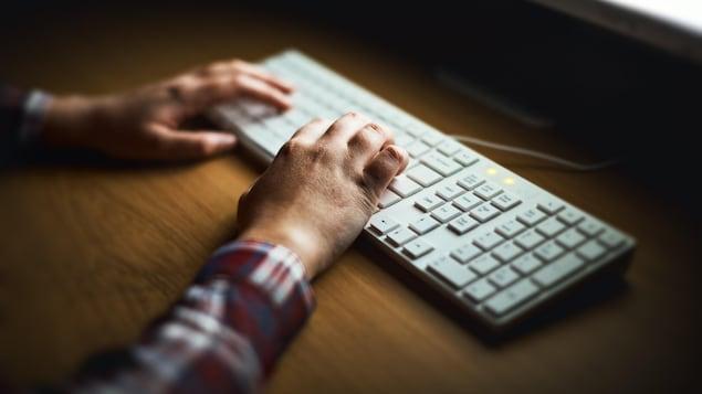 Mains d'un homme qui tape sur un clavier d'ordinateur.