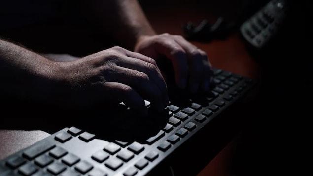 Des mains sur un clavier dans la pénombre.