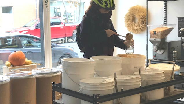 Une cliente remplit son contenant de beurre d'arachides.
