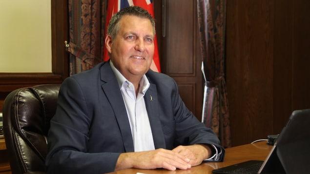 Cliff Cullen, souriant, assis à un bureau.
