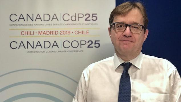Jonathan Wilkinson, devant une affiche de la COP25.