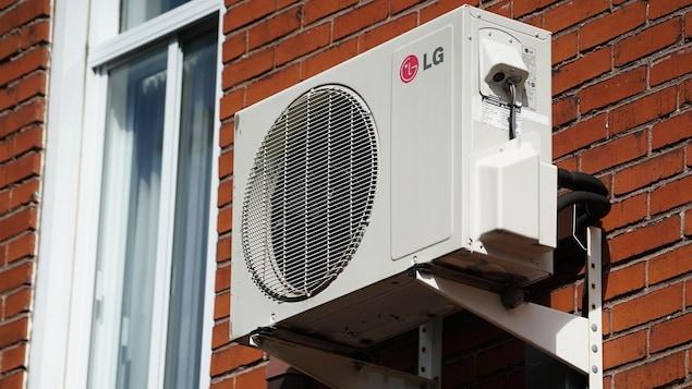 Un climatiseur installé sur un immeuble en brique