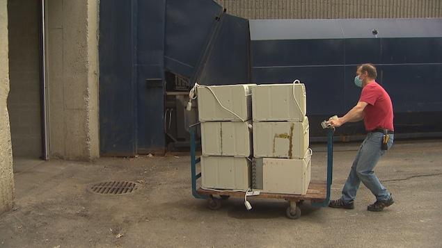 Un homme qui porte un masque transporte sur un chariot six climatiseurs.