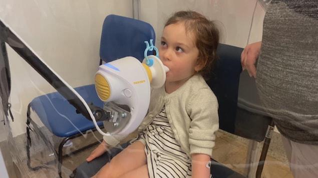 La petite fille souffle dans un appareil.