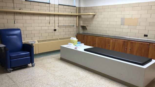 Un sofa bleu dans une salle de clinique avec un lit pour les patients