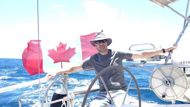 Un homme souriant assis dans un voilier.