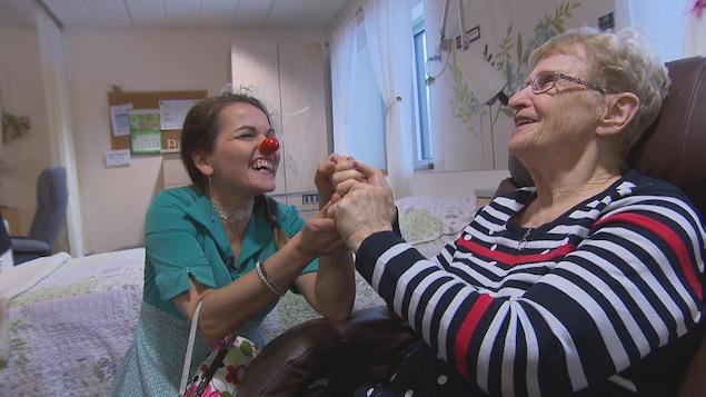 Une clown prend la main d'une dame âgée. Les deux sourient.