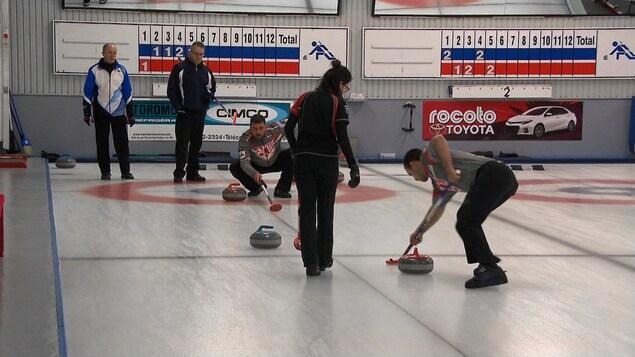 Plusieurs personnes jouent au curling.