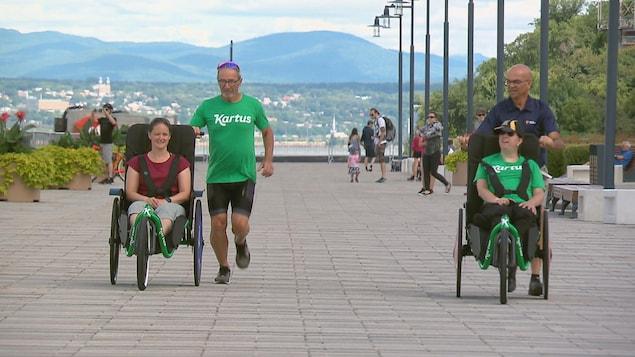 Deux personnes en fauteuil roulant adapté pour la course à pied sont poussées par des coureurs à Lévis.