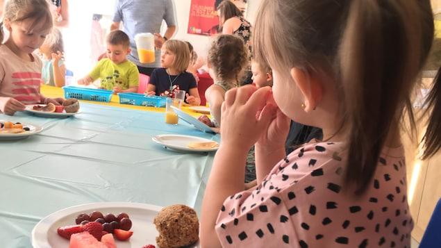 Des enfants qui mangent un déjeuner autour d'une table.