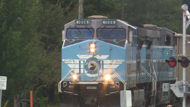 Une locomotive bleue avec des lumières allumées en avant passe sur une traverse ferroviaire.