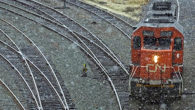 Une locomotive du CN circule sur des rails par temps pluvieux.