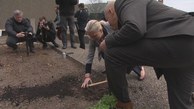 La ministre de l'Environnement et du Changement climatique, Catherine McKenna joue dans la terre sur un toit.