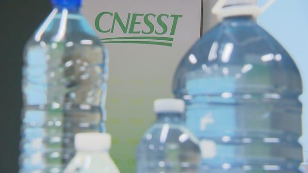 Des bouteilles d'eau devant le logo de la CNESST