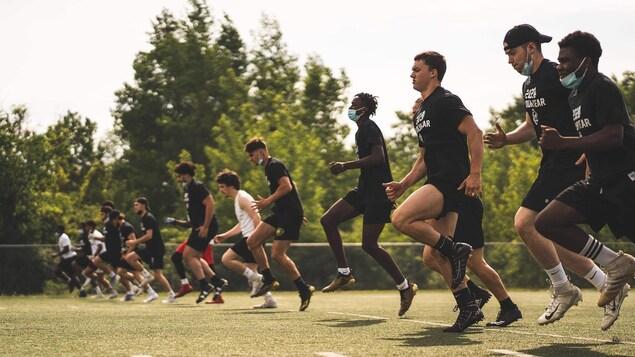 Des joueurs de football s'échauffent sur un terrain synthétique.