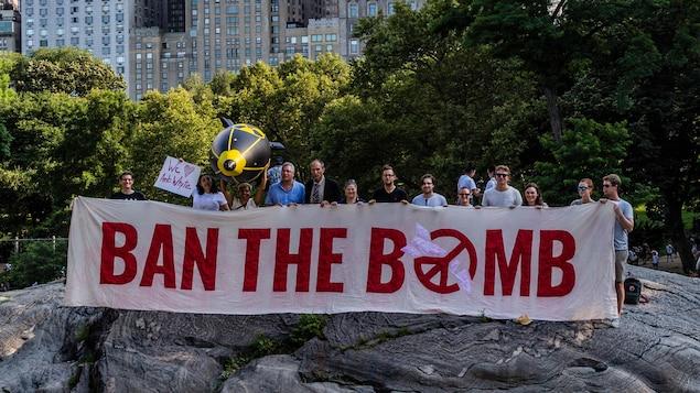 Des manifestants tiennent une bannière contre l'arme nucléaire. On y lit : « Ban the bomb ».