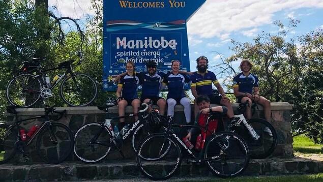 La famille Collin pose devant une affiche qui souhaite la bienvenue aux visiteurs qui entrent au Manitoba.