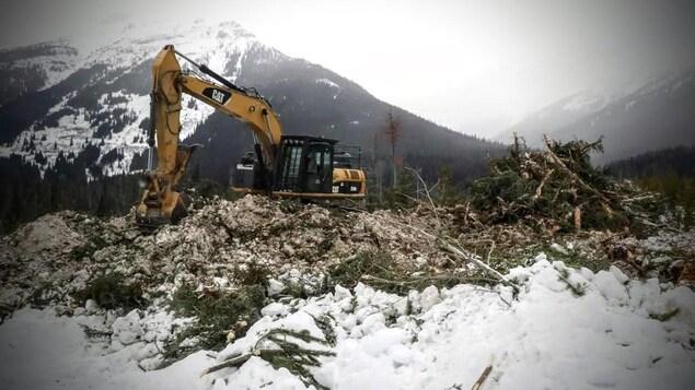 Une excavatrice sur un monticule de terre avec de la neige et la montagne en arrière plan.