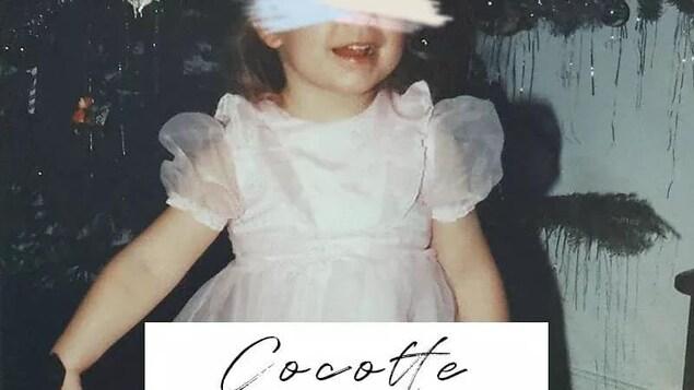 Photo d'une petite fille devant un sapin de Noël, une barre blanche dessinée devant ses yeux.