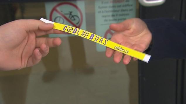 Le fameux bracelet « Code Bars » : il est jaune et s'attache autour du poignet.