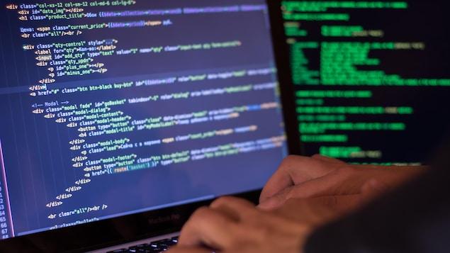Un homme tape des lignes de code sur un ordinateur portable.