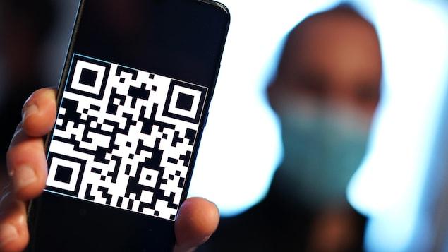 Une personne portant un masque tient son téléphone cellulaire, sur lequel s'affiche un code pixellisé.