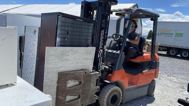 Un réfrigérateur est transporté par un chariot.