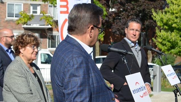 Denis Coderre en point de presse dans un parc, entouré par ses candidats dans l'arrondissement de Villeray-Saint-Michel-Parc-Extension.
