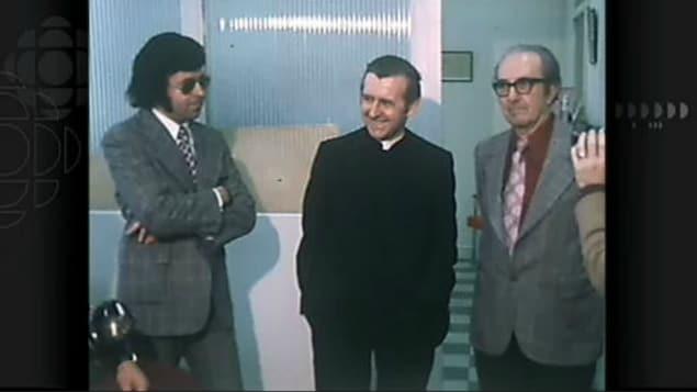 Deux hommes et un prêtre debout.