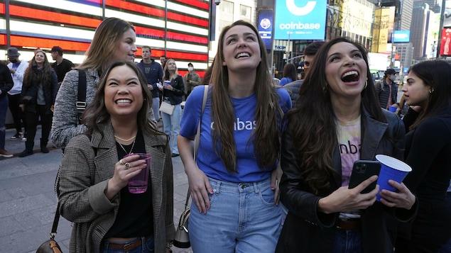 Des jeunes femmes lèvent les yeux aux ciel pour regarder les résultats et sourient.
