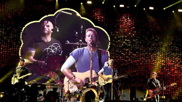 Les membres du groupe chantant et jouent devant des projections.