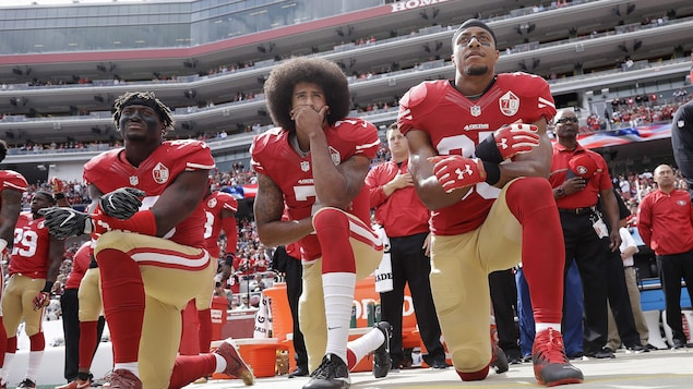 Colin Kaepernick et deux autres joueurs de football agenouillés