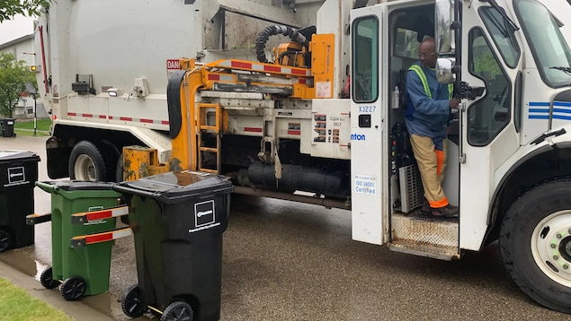 Une benne ordures lève un bac de couleur vert.