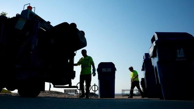 Un camion à ordure et deux employés
