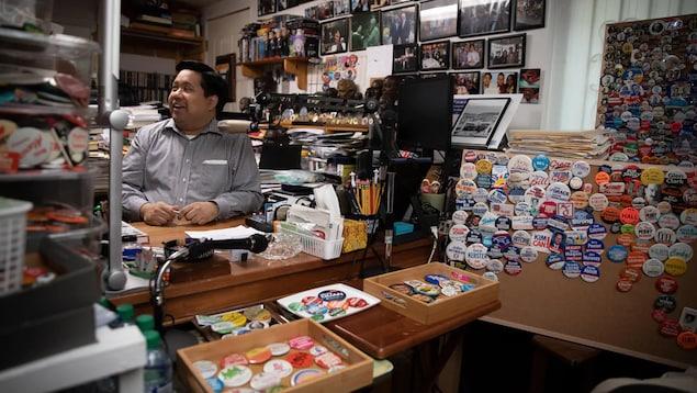 Joseph Planta est debout dans une pièce remplie d'objets aux couleurs de différents partis politiques et candidats.