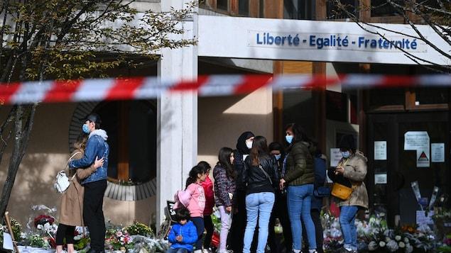 Plusieurs personnes sont rassemblées devant les portes d'un collège, où ont été placées de nombreuses gerbes de fleurs. Parmi eux, des enfants et un couple qui s'enlace.