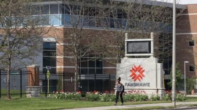 Une femme marche avec un sac devant le collège Fanshawe.