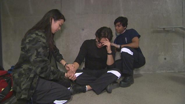 Une étudiante prend le pouls d'un autre étudiant pendant qu'un camarade de classe l'ausculte avec un stéthoscope.