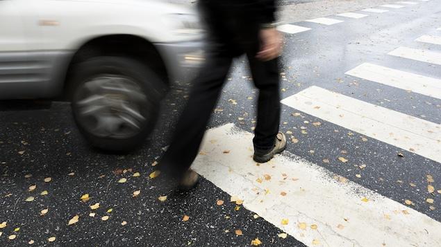 Un piéton marche sur une traverse alors qu'un véhicule passe rapidement à côté de lui.